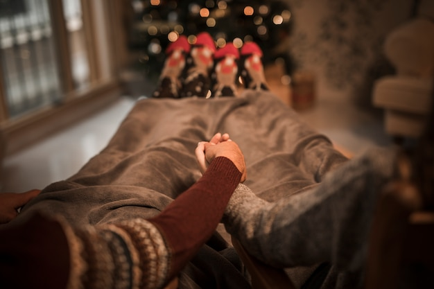 Man and woman holding hands and lying near christmas tree
