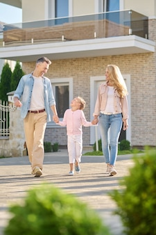 Man and woman holding hands walking daughter happy