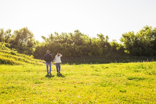 Man and woman holding hands and walking on nature back view