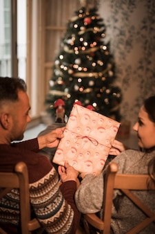 Man and woman holding present box on chairs near christmas tree