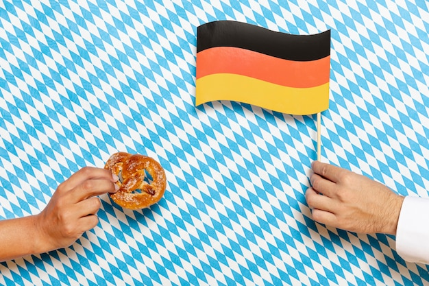 Man and woman holding pretzel and flag
