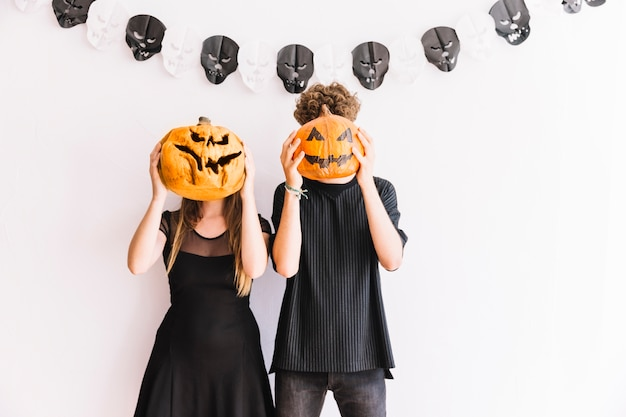 Man and woman holding pumpkins before faces