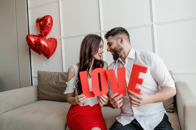 Man and woman holding red love letters with heart shaped balloons at home sitting on couch
