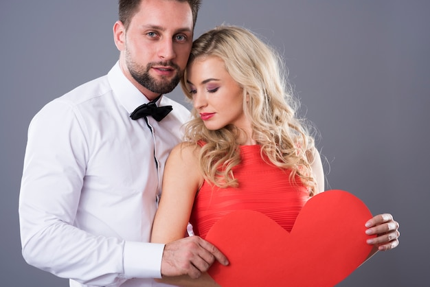 Uomo e donna che tengono cuore di carta rosso