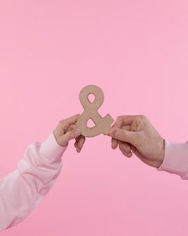 Man and woman holding symbol of ampersand
