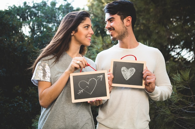 Man and woman holding two blackboards with drawn hearts