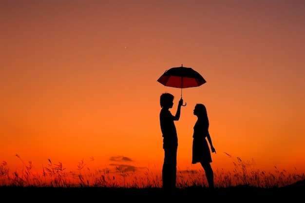 Man and woman holding umbrella in evening sunset
