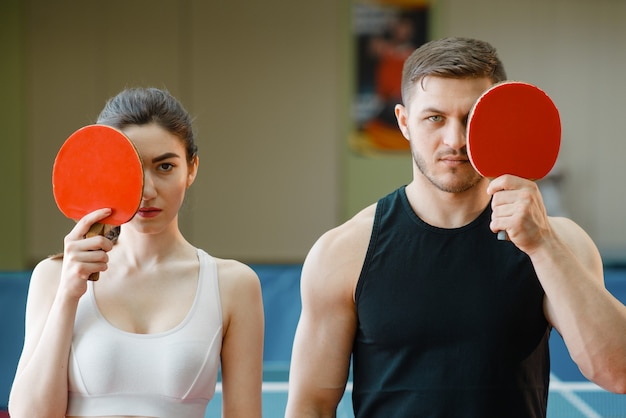 Man and woman holds ping pong rackets indoors.