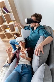 Uomo e donna a casa sul divano utilizzando l'auricolare per realtà virtuale