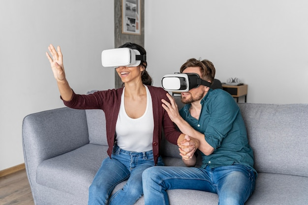 Man and woman at home on the couch with virtual reality headset
