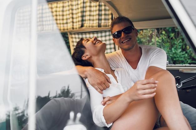 Abbracciare l'uomo e la donna e sorridere seduto in un vecchio autobus