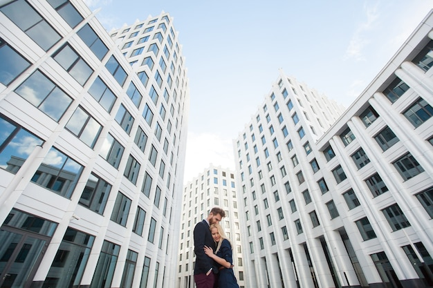 Man and woman hugging in the background is the building of the business center.