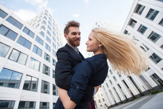 Man and woman hugging and laughing in front of a white building. bottom view