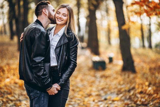 Man and woman hugging and smiling in autumn park.