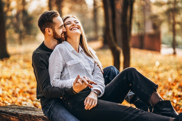 Man and woman hugging and smiling on autumn trees.