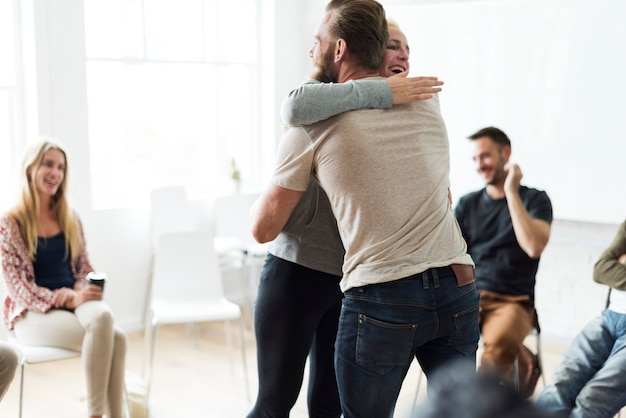 Man and woman hugging in a support group