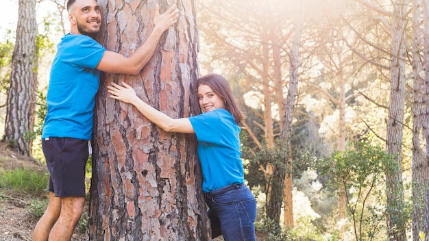 Man and woman hugging tree in lovely forest