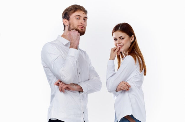 A man and a woman in identical shirts are gesticulating with their hands on a light background
