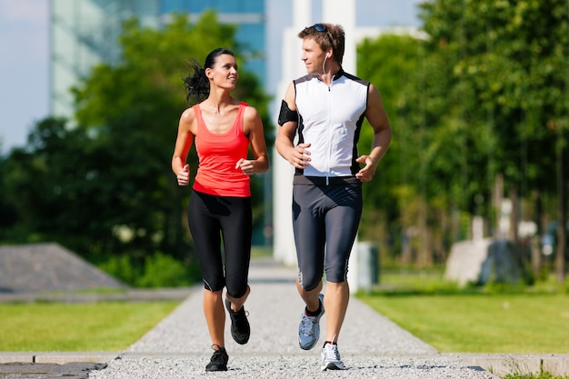 Man and woman jogging for fitness in the city