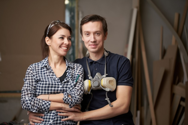 Man and woman joiners sitting in workshop on background of boards