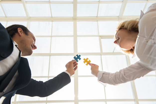 Man and woman joining jigsaw pieces of puzzle in office.