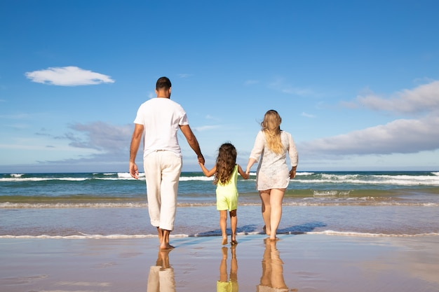 Man, woman and kid wearing pale summer clothes, walking on wet sand to sea, spending leisure time on beach