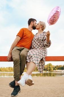 Uomo e donna che si baciano mentre sono seduti e che tengono un palloncino cuore rosa con il cielo