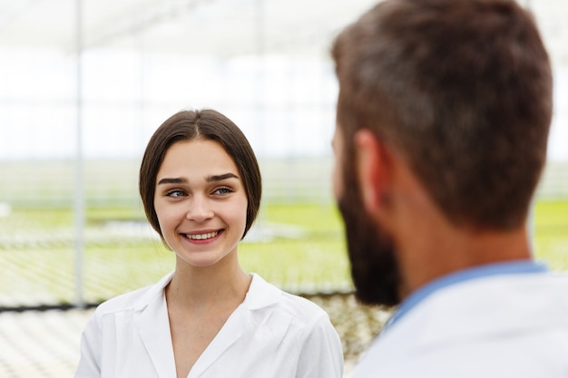 Man and woman in laboratory robes talk to each other standing in the greenhouse