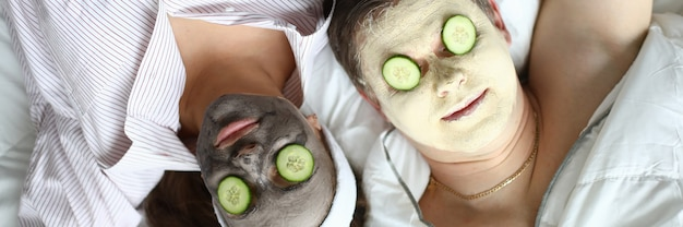 Man and woman lay on white pillow in opposite direction. face close up cosmetic mask and cucumber slice on eyes.