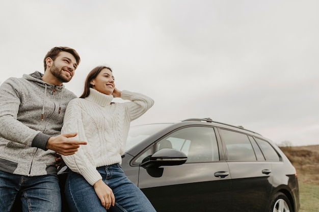 Man and woman leaning on car