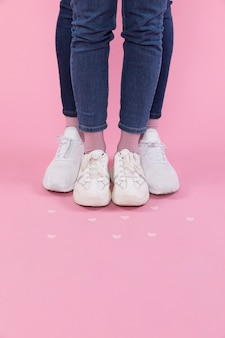 Man and woman legs in jeans and sneakers near decorative hearts