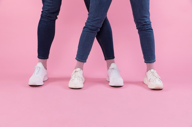 Man and woman legs in jeans and sneakers