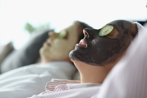 Man and woman lie with cosmetic mask on their faces and slices of cucumbers on their eyes.