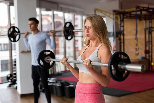 Man and woman lifting weights bar