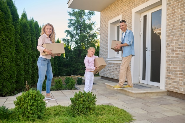 Man woman and little girl with boxes near house