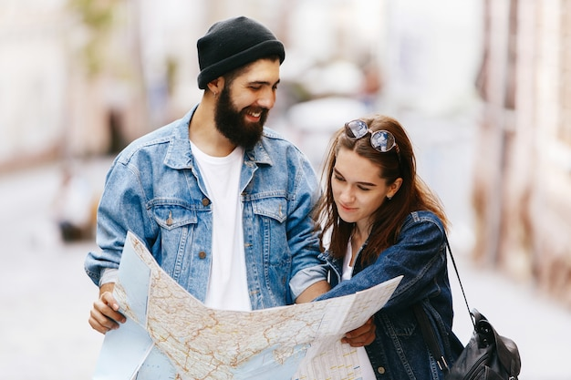 Man and woman look at the map standing somewhere in an old city