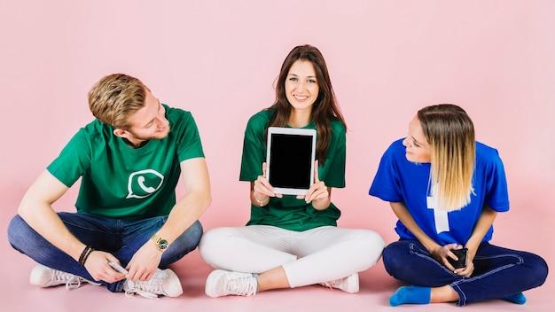 Uomo e donna che esaminano il suo amico femminile felice che mostra compressa digitale