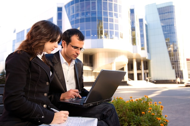 Man and woman looking at laptop screen and sitting on bench in front of office building in sunny weather