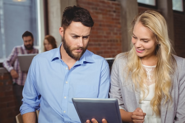 Man and woman looking towards digital tablet