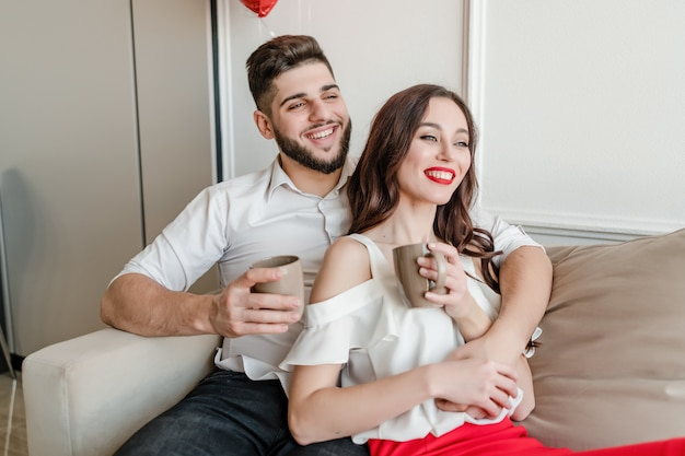 Man and woman in love drinking from cups in the morning on couch at home