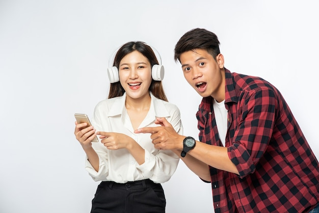 Man and woman love listening to music on their smartphones