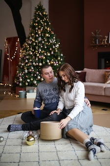 A man and a woman in love open and give gifts sitting on the floor by the tree in a cozy home