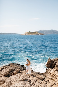 Man and woman in love stand embracing on the rocky seashore behind them is the
