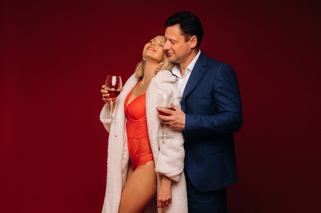 A man and a woman in love with a glass of champagne on a red background embrace.
