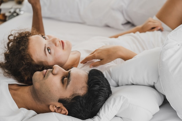 A man and a woman lying on a bed