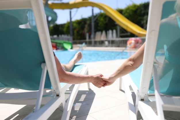Man and woman lying on sun loungers near swimming pool and holding hands back view