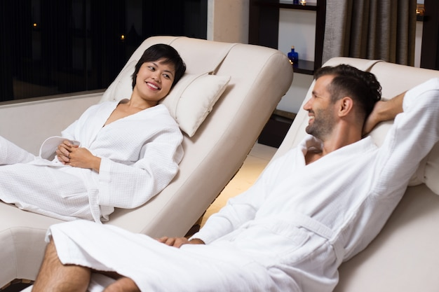 Man and woman lying in white coats