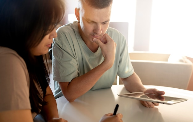 Man and woman making shopping list with tablet