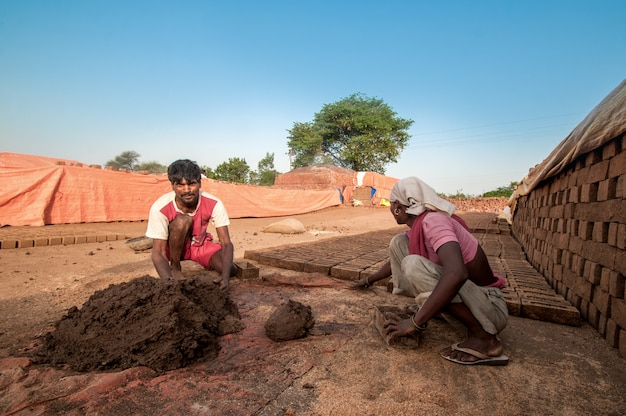 Man and woman making in traditional bricks of clay in brick factory