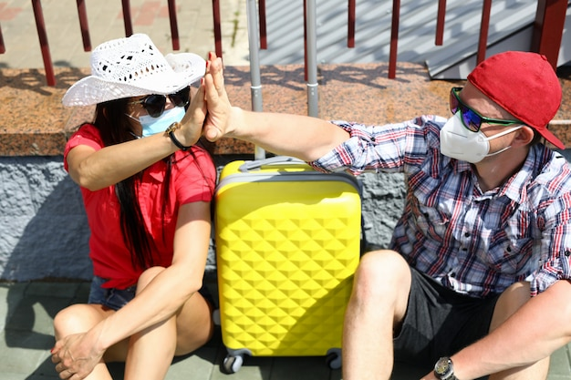 Man and woman in medical masks with suitcase go on trip.